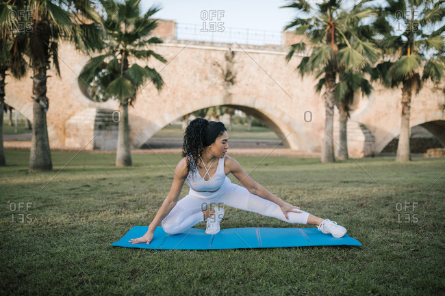 Sportswoman stretching on exercise mat over grass at public park