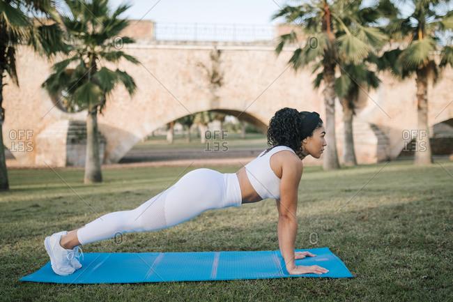 Sportswoman exercising on exercise mat in public park