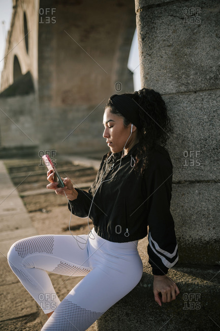 Female athlete listening music while using mobile phone on retaining wall in park