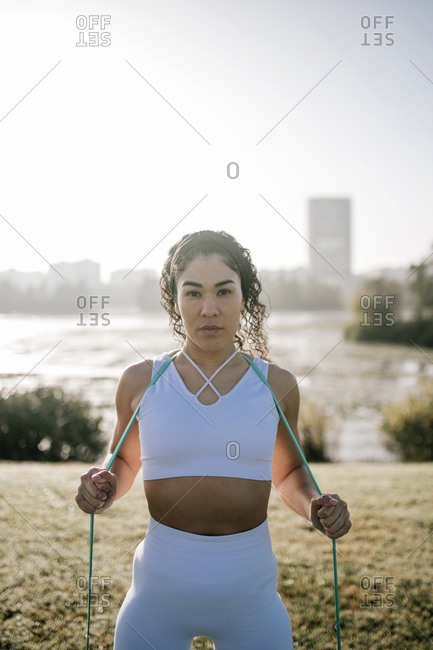 Female athlete with resistance band against clear sky at public park
