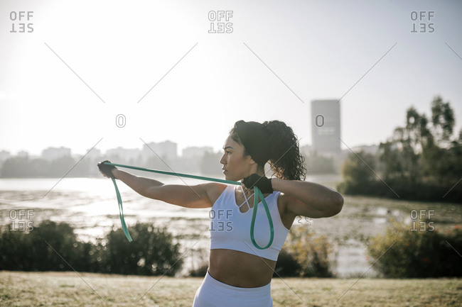 Female athlete stretching resistance band while exercising in public park against clear sky