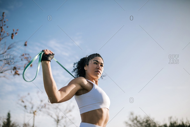 Sportswoman looking away while stretching resistance ban against sky
