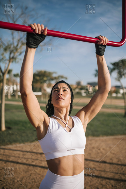 Female athlete with arms raised holding red pole in public park on sunny day