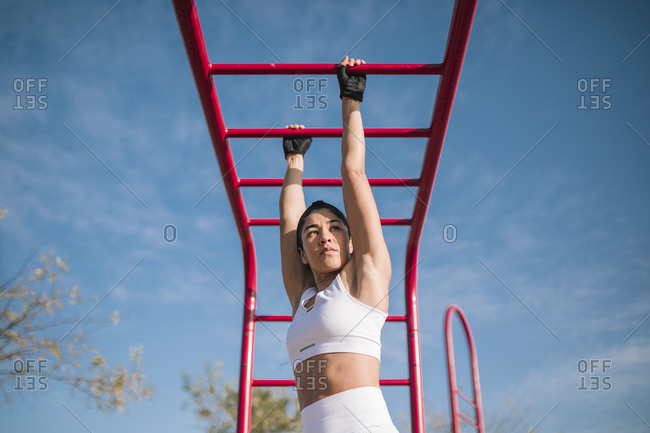 Confident sportswoman hanging on monkey bars while sports training in public park