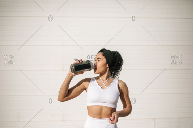 Sportswoman drinking water against wall on sunny day