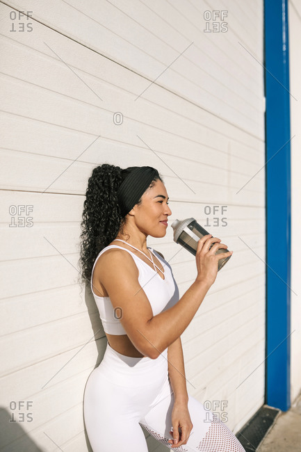 Smiling female athlete with water bottle leaning on wall during sunny day