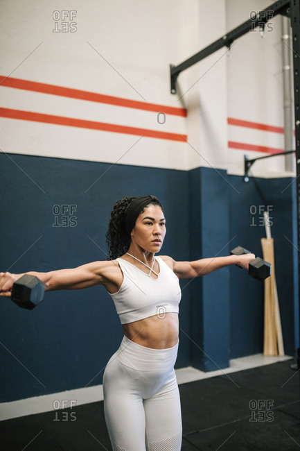 Confident sportswoman training with dumbbells in gym