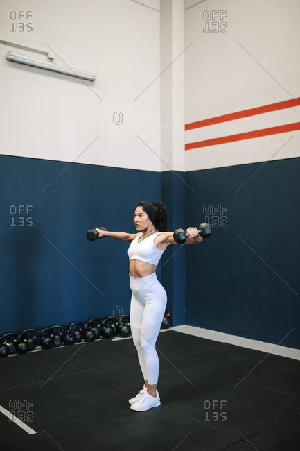 Sportswoman with arms raised exercising dumbbells in gym