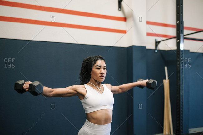 Female athlete working out with dumbbells against wall in gym