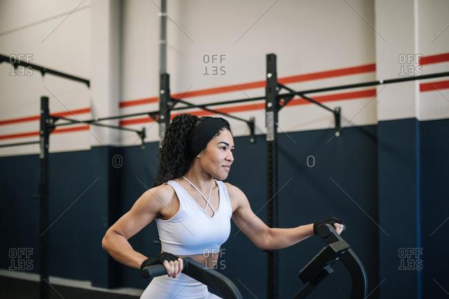 Smiling sportswoman exercising on exercise bike in gym