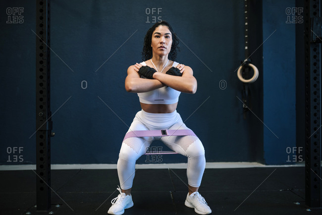 Sportswoman with resistance band in gym against wall