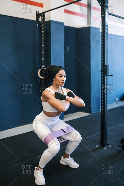 Confident female athlete working out with resistance band in gym