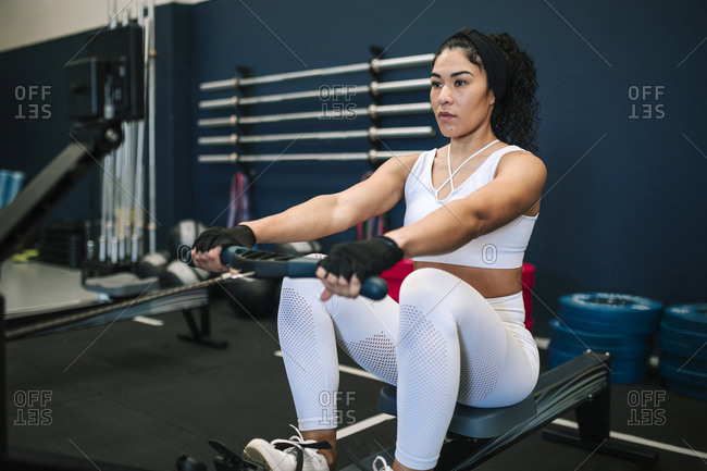 Confident sportswoman pulling rowing machine while training in gym