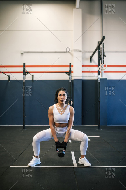 Sportswoman with dedication lifting up kettlebell in gym