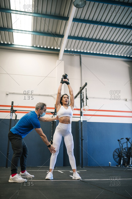 Male fitness instructor training sportswoman with kettlebell in gym during COVID-19