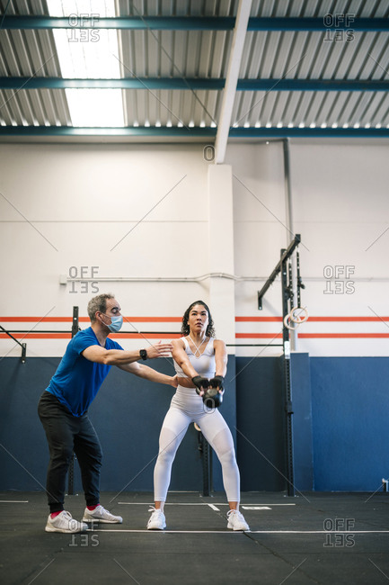Male fitness instructor training female athlete with kettlebell in gym during COVID-19