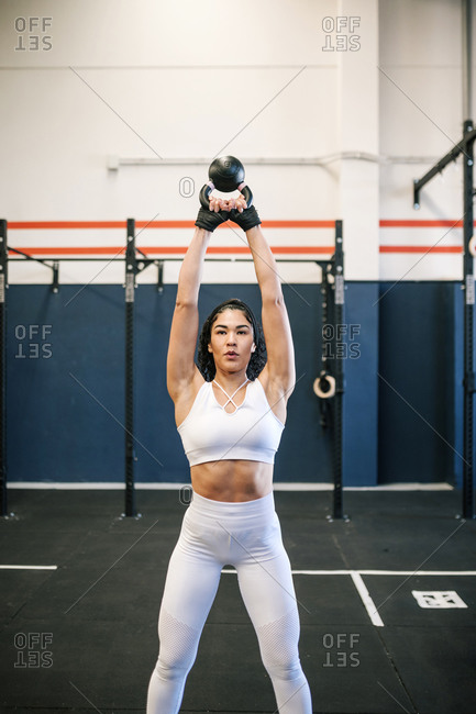 Confident female sportsperson exercising with kettlebell in gym