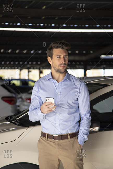 Male entrepreneur with hand in pocket holding mobile phone while standing at parking lot