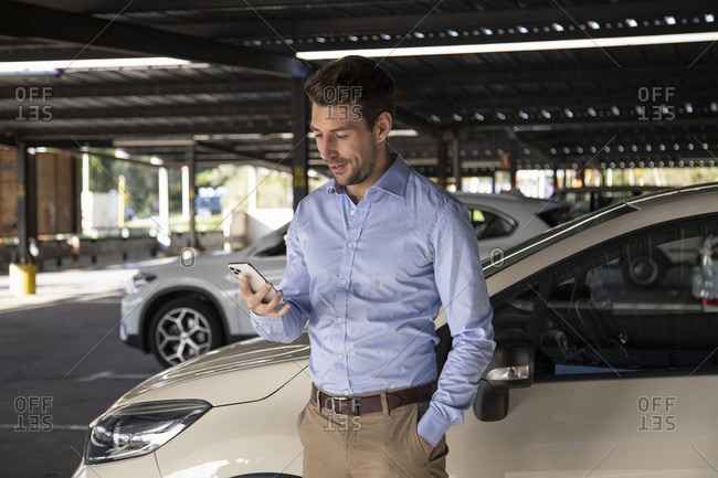 Smiling businessman using mobile phone while standing in parking lot
