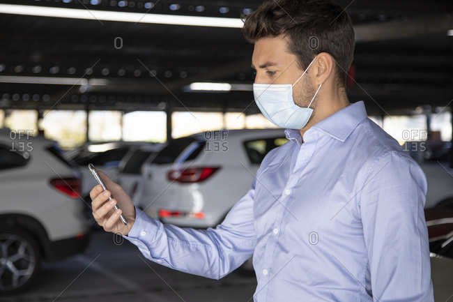 Male entrepreneur using mobile phone in parking lot during pandemic