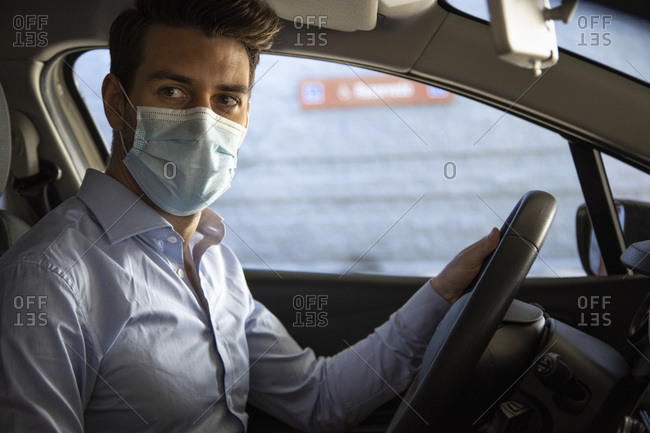 Male entrepreneur with protective face mask looking away while sitting in car during pandemic
