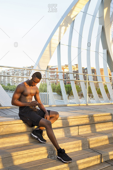 Young sportsman using smart phone while sitting on steps over bridge