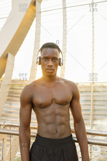 African male athlete listening music through headphones while standing against railing