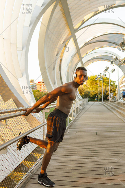 Male athlete leaning on railing while standing over bridge