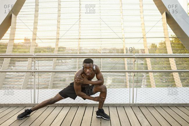 Confident sportsman doing stretching exercise on bridge