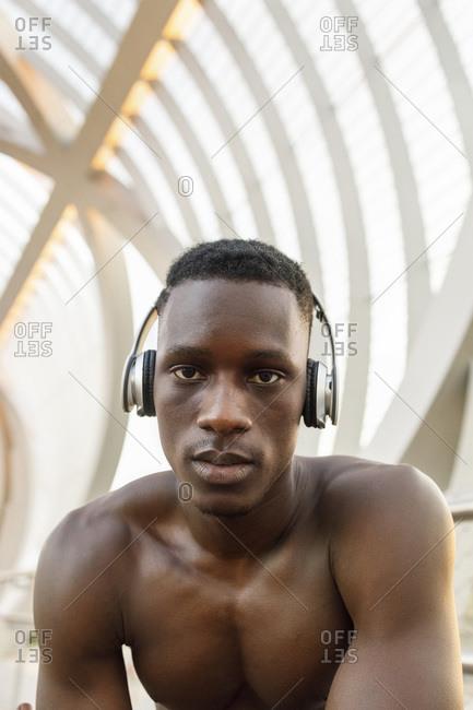Male athlete listening music through headphones over bridge