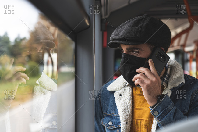 Commuter wearing protective face mask on phone call in bus