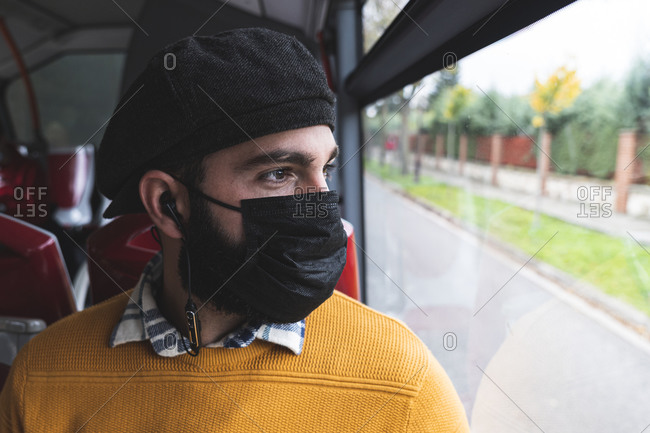 Commuter looking through window while listening music in bus