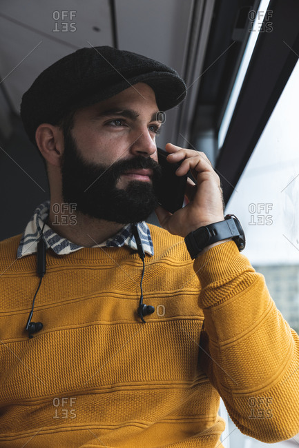 Commuter in sweater talking on mobile phone in bus