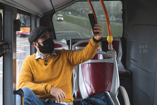 Businessman taking selfie with mask on face while commuting in bus