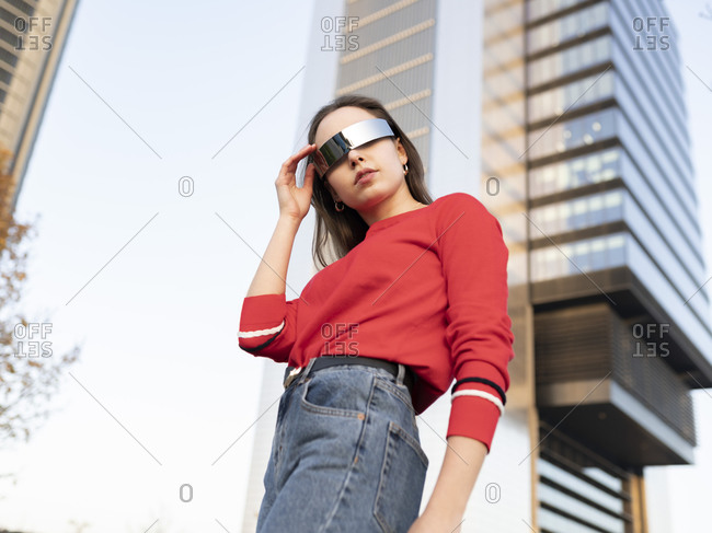 Woman wearing sunglasses standing against building in city