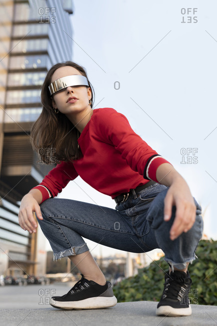 Elegant woman with sunglasses crouching on footpath in city