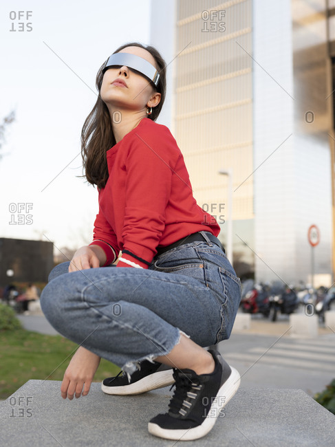 Young woman wearing sunglasses crouching on footpath in city