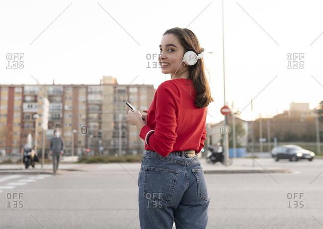 Woman with listening music through headphones while standing on street in city