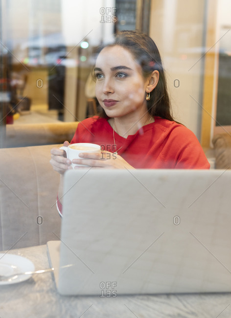 Young woman with coffee cup seen through glass in cafe