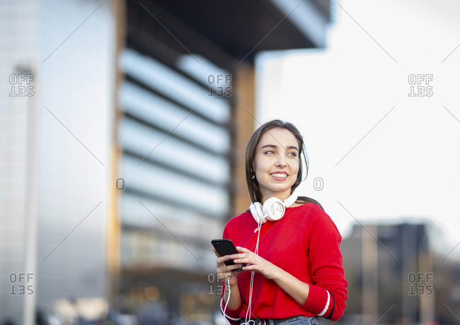 Smiling woman with headphones and mobile phone in city