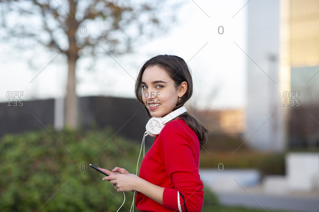 Young woman with headphones and smart phone in park