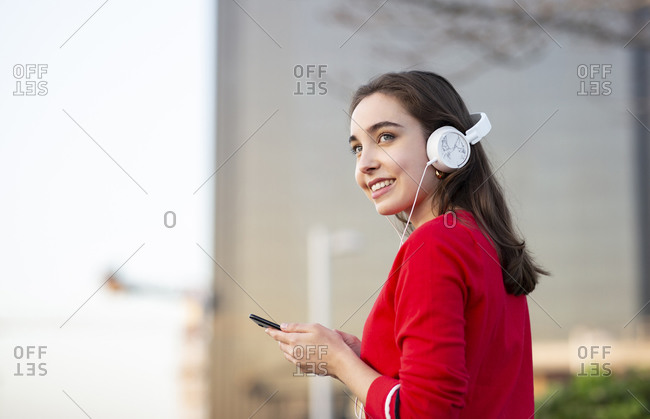 Smiling woman listening music through headphones while holding smart phone