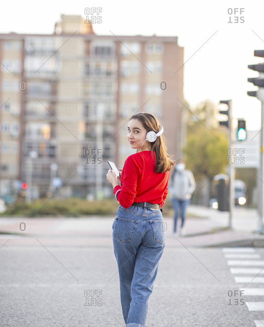 Woman listening music through headphones while standing on street in city