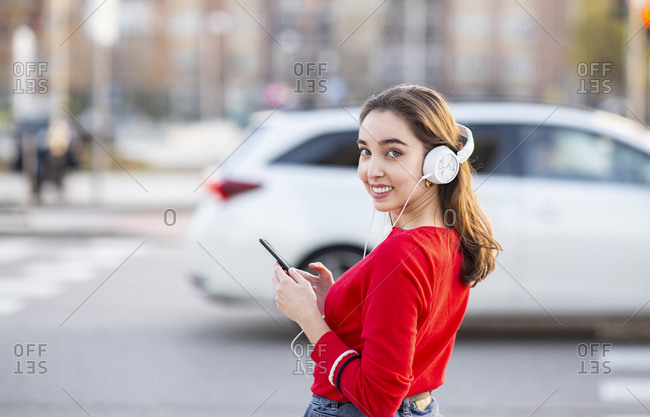 Smiling woman listening music through headphones while standing on street in city