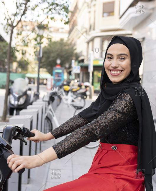 Portrait of young woman wearing hijab sitting on rental bike