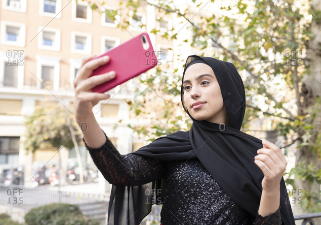 Portrait of young beautiful woman wearing black hijab taking smart phone selfie