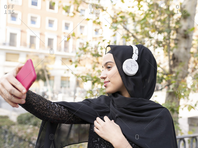 Portrait of young beautiful woman wearing hijab and headphones taking smart phone selfie