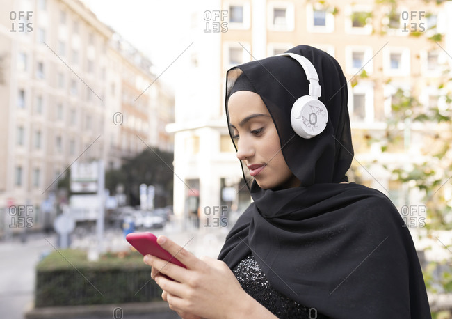 Portrait of young beautiful woman wearing hijab and headphones using smart phone