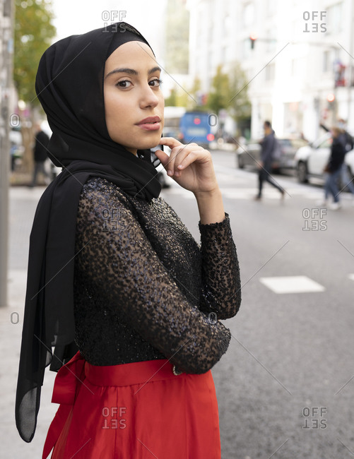 Portrait of young beautiful woman wearing black hijab posing on city street