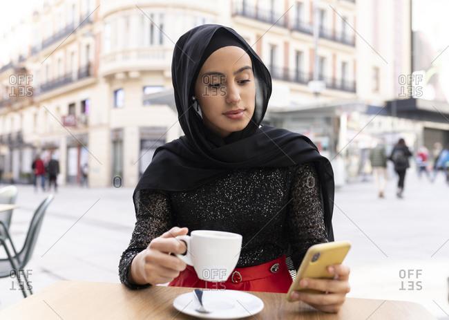 Portrait of young beautiful woman wearing black hijab using smart phone at sidewalk cafe